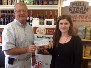 Norman Picton, a Bay Treasure Chest Volunteer and Committee member, presents a cheque for $1,481 to Laura Merrimen at Delish Fine Foods in Tantallon, where she works.