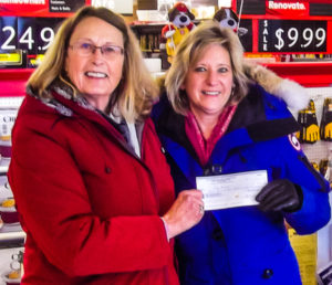 Ruth Ann Moger (L) from Bay Treasure Chest presents a cheque for $3,382 to Lily Mahar (R)