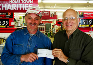 Phil Lively (L) is presented with a cheque by Fred Dolbel (R), a Bay Treasure Chest Volunteer.