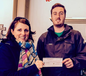 Julie Stover (L), Bay Treasure Chest Volunteer presents cheque for $3,641 to Shawn MacDonald (R) at Hubley Pizza, where he played his lucky Toonie.