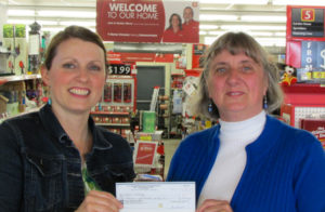 Diane Whiting (R) receives her winner's cheque from Julie Stover (L), Bay Treasure Chest volunteer at Redmond's Home Hardware
