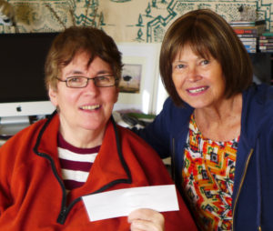 Minette Nortje (L) receives her cheque from Anne Martell, a Bay Treasure Chest volunteer