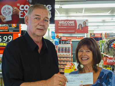 Peter MacAulay (L) receives his winner's cheque for $12,509 in Redmond's Home Hardware from Anne Martell (R), a Bay Treasure Chest volunteer