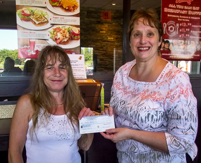 Lynn Coward (R), from Bay Treasure Chest, presents a cheque to our winner Carolin Dauphinee for $15,709 with #2314!