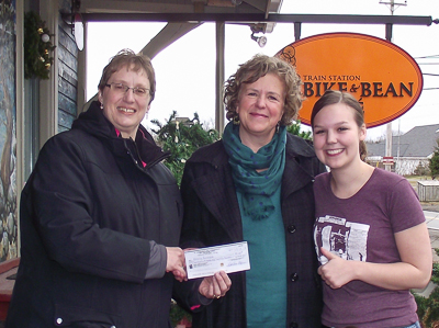 Lynn Coward, Bay Treasure Chest Volunteer presenting cheque to Patricia (M) with Emma Paul (R) of the Bike & Bean Cafe.