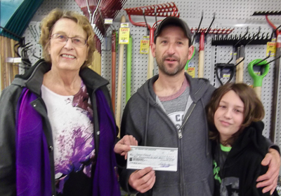 Darrin (M) and son (R) receiving his cheque from Ruth Ann Moger (L), Bay Treasure Chest Volunteer