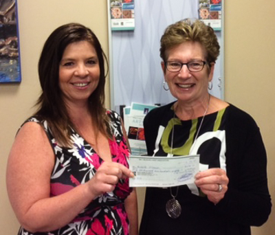 Michelle (L) receiving her cheque from Susan Picton (R), Bay Treasure Chest Volunteer