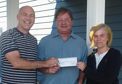 Paul (L) and Elise (R) Fieldhouse receive their winning cheque from Harry Ward (M), Bay Treasure Chest Volunteer