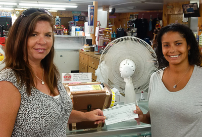 Michelle (L) receiving her winning cheque from Chanice Johnson (R), Bay Treasure Chest Volunteer