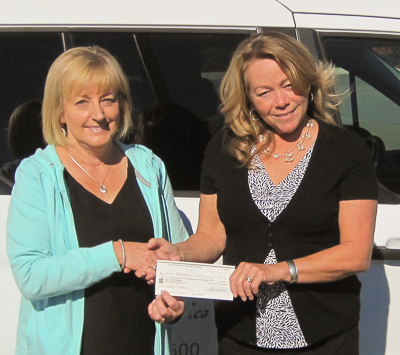 Pictured in front of the BayRides van our October 5th winner Renée Robertson (L) receives her cheque from BTC Volunteer Dianne Lanteigne (R).