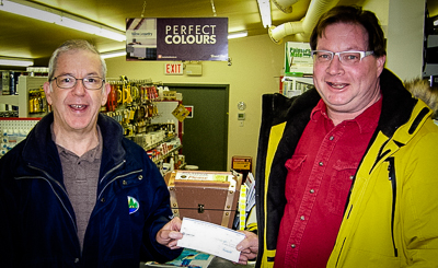Billy (L) receiving cheque from Bay Treasure Chest Volunteer, Harry Ward (R)
