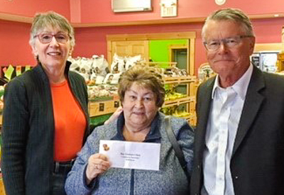 Anne Patrick (L) and Richard Muzyk (R), Bay Treasure Chest Volunteers, present the April 5 winner's cheque to Brenda Balser (C)