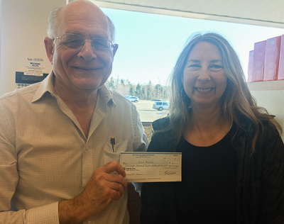 Fred Dolbel (L) present the April 12 winner's cheque to Diana Harrison