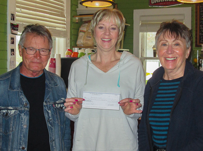 Daralynne Lewis (C) receives her May 31 winner's cheque for $8,901 from BTC volunteers Rick Muzyk (L) and Anne Patrick (R)