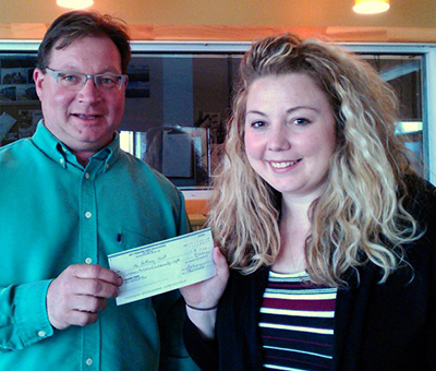 Brittney Short (R) receives her May 24 winner's cheque from BTC volunteer Harry Ward