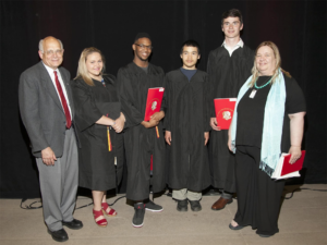 Fred Dolbel and Gwen Colman from Bay Treasure Chest Association present the Anne Martell Memorial Scholarship Awards to four Sir John A. MacDonald students