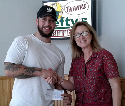 Mich Isshac (L) receives his July 12 winner's cheque from BTC volunteer Heather Cochrane